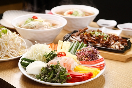 ingredients for vietnamese spring roll such as sprouts, perilla leaves on round plate, with grilled pork on iron plate