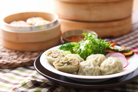 boiled dumplings on round plate, dumplings in steamer