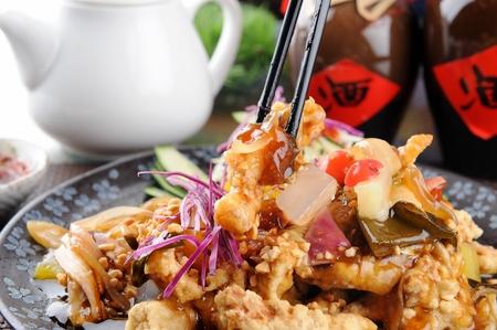 Bacchette che afferrano maiale in agrodolce con ananas e cipolle, su piatto rotondo