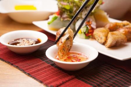 chopsticks dipping cha gio in fish sauce Banco de Imagens