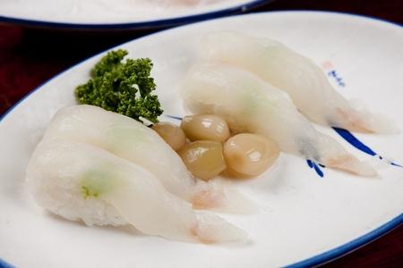 flatfish sushi with scallions, on round plate