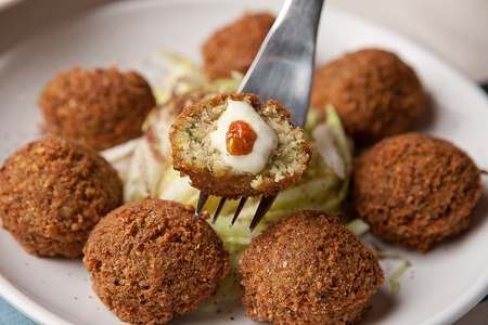 fork grabbing half a croquette with sauce Stockfoto