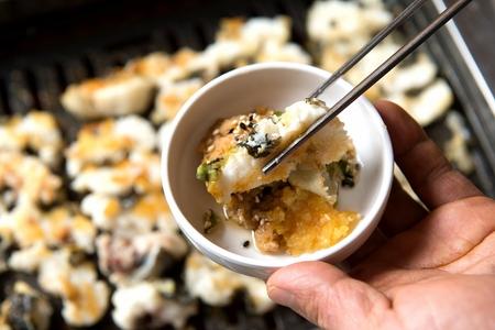 chopsticks dipping eel in sauce Reklamní fotografie