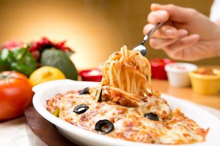 fork grabbing tomato cheese spaghetti