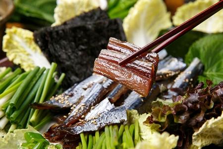chopsticks grabbing half-dried herring from cabbage Foto de archivo