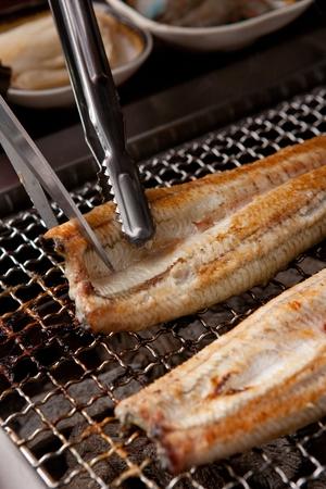 scissors cutting grilled eel on gridiron