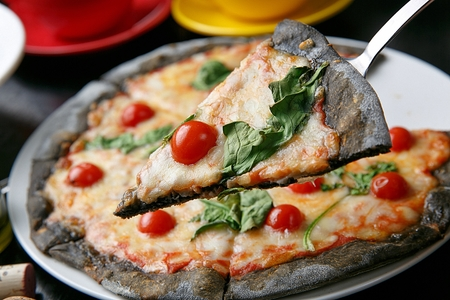 spatula scooping up pizza with cherry tomatoes and vegetables