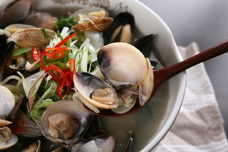 spoon scooping up seashells from seafood ramyun