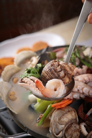ladle scooping up seafood from seafood hot pot