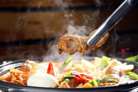 pincers grabbing drumstick from braised spicy chicken with vegetables