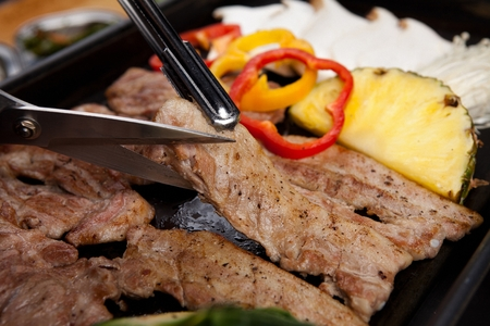marinated pork, pineapples and mushrooms being grilled on iron plate Фото со стока