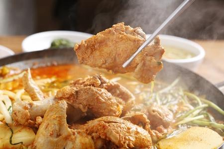 chopsticks grabbing chicken meat from braised spicy chicken with vegetables