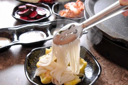 Zange, die Reisnudeln verteilt Standard-Bild