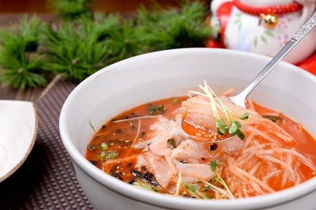 spoon scooping up cold raw fish soup and vegetables