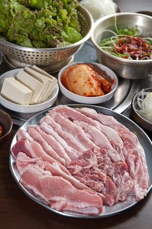Raw pork with side dish including spring onion and tofu
