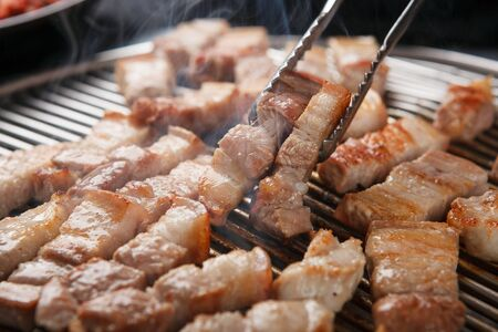 Grilled pork belly grabbed with pincers