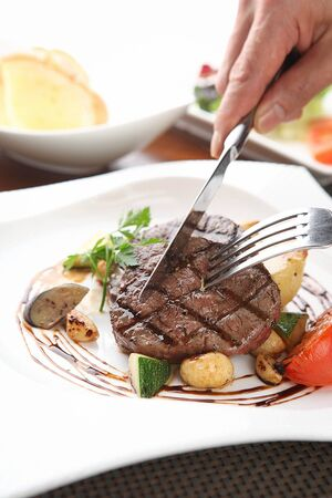 Knife and fork cutting beef tenderloin steak with vegetables