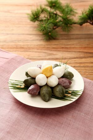 Green, violet, white, and green half moon shaped rice cake served on grey plate Imagens
