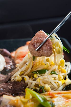 Chopsticks holding bean sprouts and grilled entrail assortment