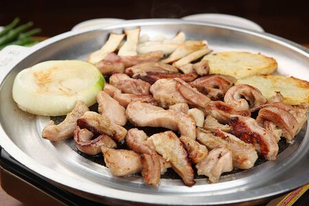 Grilled intestines with onions, potatoes and chives on grill 免版税图像