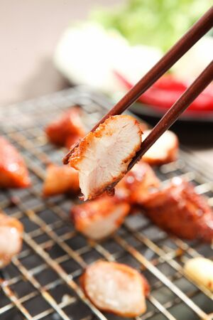 Chopsticks grabbing lamb tripe being grilled on grill