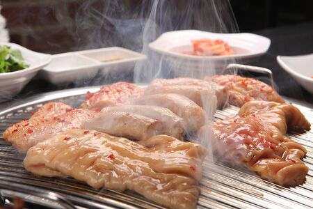 Sauced lamb tripe being grilled on grill