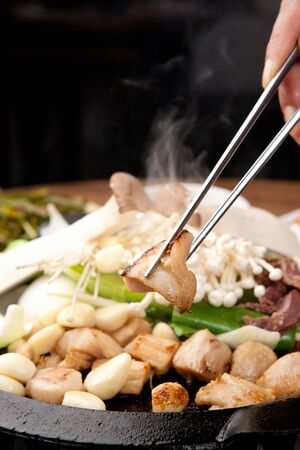 Chopsticks grabbing grilled entrail assortment cooked on grill