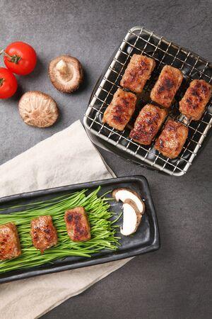 Grilled Korean short rib patty and vegetables on plate with grilled Korean short rib patty on grill Banco de Imagens