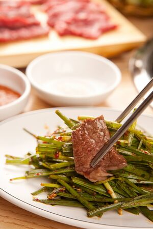a slice of beef grabbed with chopsticks, with raw sirloin, vegetables and sauce