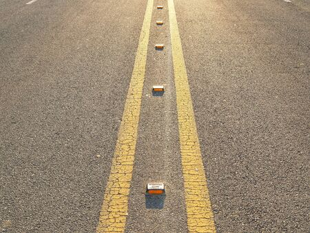the centerline of the asphalt road at sunset