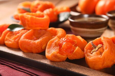 dried persimmons on wood plate Imagens