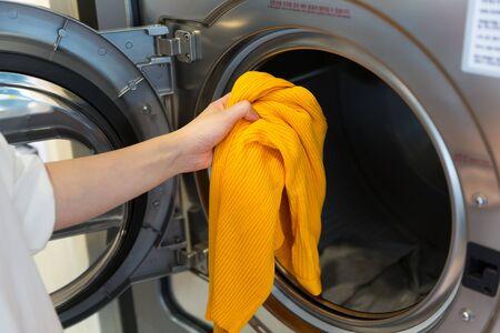 Single life concept, washing clothes at laundromat