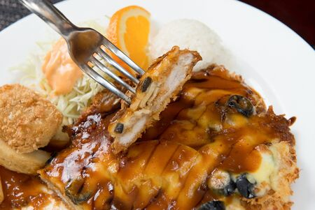 Donkatsu with olive and cheese on fork