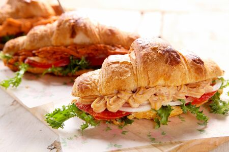 tuna croissant sandwich with tomato and onion on a cutting board