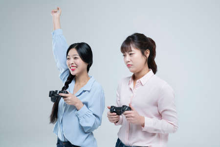 two Asian women, sisters playing video games with game controllers