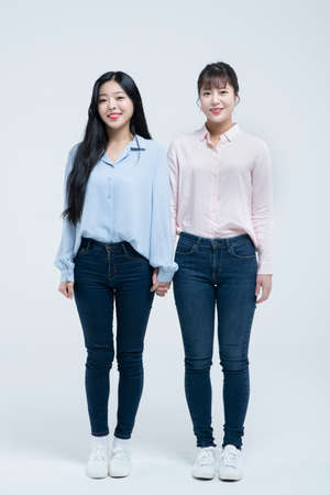 two Asian women standing and holding hands, white background Standard-Bild