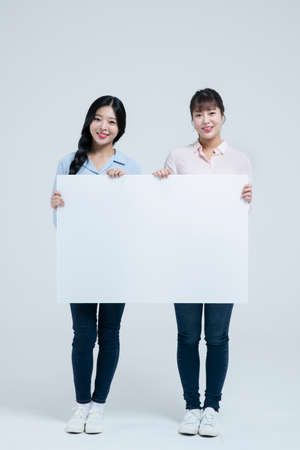 two smiling asian woman holding hite board with copyspace
