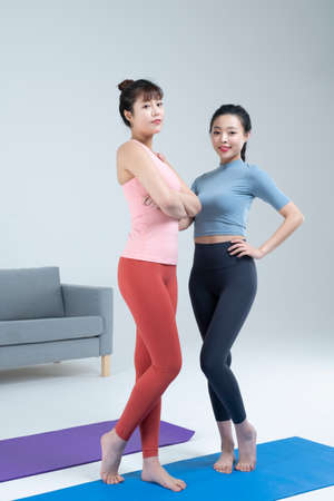 two fit Asian young women home training concept wearing sports top and leggings
