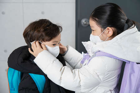 Asian boy and girl wearing mask before going to school Stock Photo