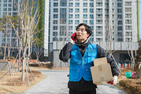 Asian delivery man with mask on phone with customer