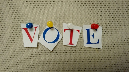 Red white blue letters pinned on a board that spells vote Stock Photo