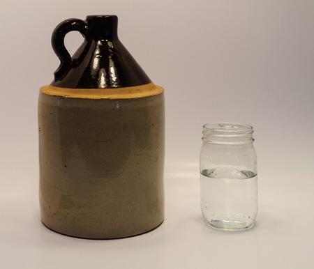 Moonshine jug and mason jar Stock Photo