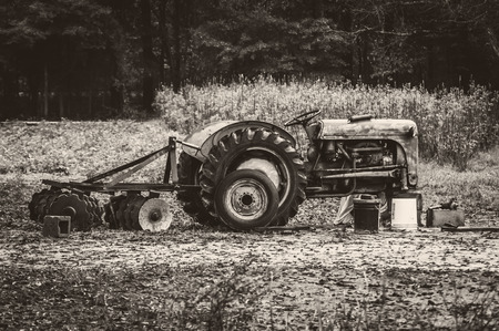 Old Farm Tractor In Field, In Need Of A Wheel Repair Stock Photo