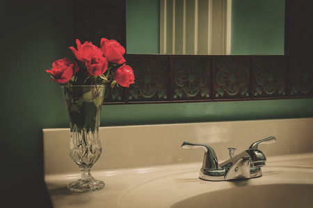 Red Rose In Vase On A Bathroom Counter Top