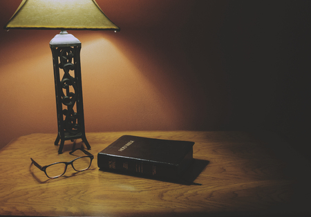 Holy Bible On Wood Table With Glasses Under Lamp