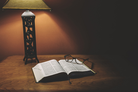 Open Holy Bible On Wood Table With Glasses Under Lamp Light