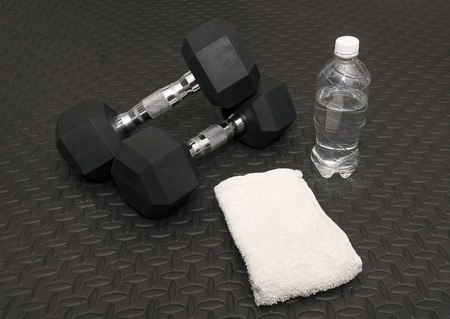 Arm Weights, Sweat Towel And Water Bottle On Workout Rubber Mat