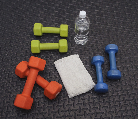 Colorful Hand Weights, Towel And Water On Workout Mat Stock Photo