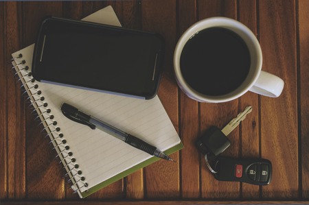 Cup Of Coffee, Cell Phone, Notepad, Pen, And Keys On A Wood Table Stock Photo