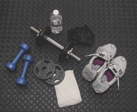 Weights, Water, Towel, Gloves And Shoes Laying On Workout Mat